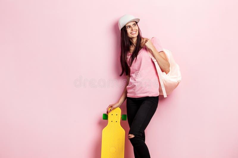 A menina bonita no tampão branco e com uma trouxa em seu ombro vestido no t-shirt cor-de-rosa e em calças de brim pretas está com imagens de stock