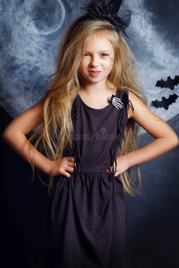 Menina bonita no traje da bruxa de Dia das Bruxas imagens de stock royalty free