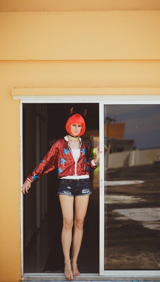 Menina bonita no traje do diabo que está em um corredor sombrio pela janela Veste uma peruca vermelha com chifres, short da sarja fotografia de stock
