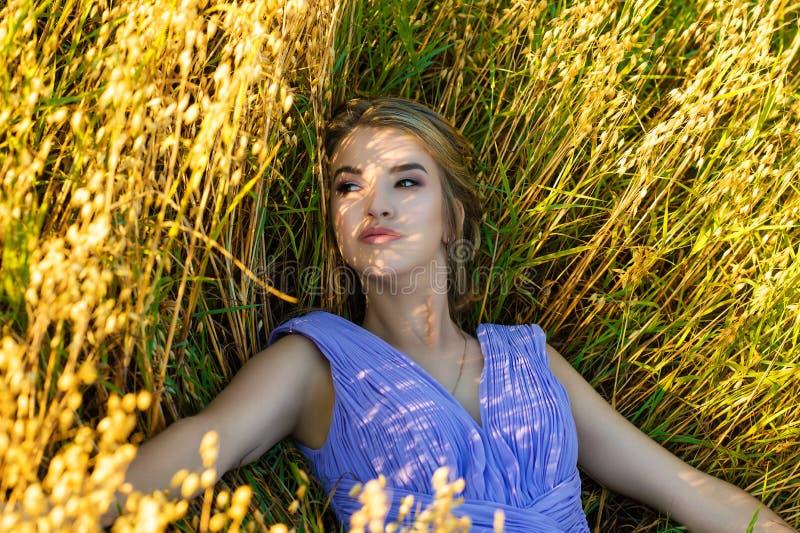 Menina bonita no vestido azul que encontra-se no centeio fotografia de stock