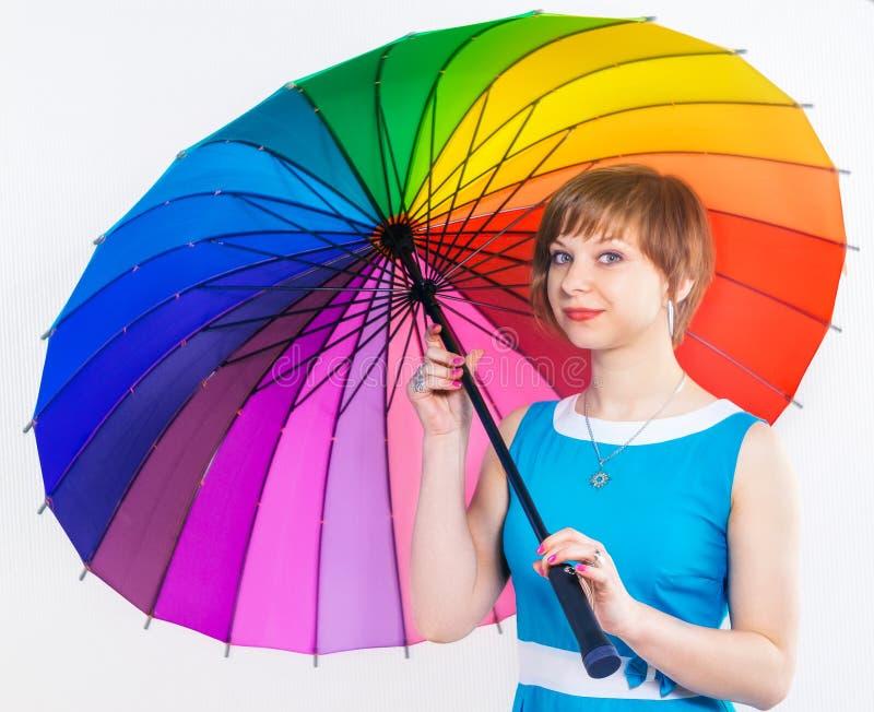 Menina bonita no vestido azul sob o guarda-chuva positivo colorido do arco-íris no fundo branco Tiro do estúdio, espaço da cópia foto de stock