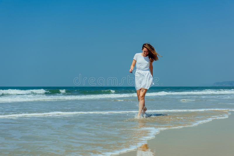 A menina bonita no vestido branco aprecia e relaxa na praia Curso e f?rias fotos de stock