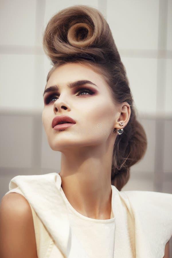 Menina bonita no vestido branco com cabelo encaracolado no cinza foto de stock