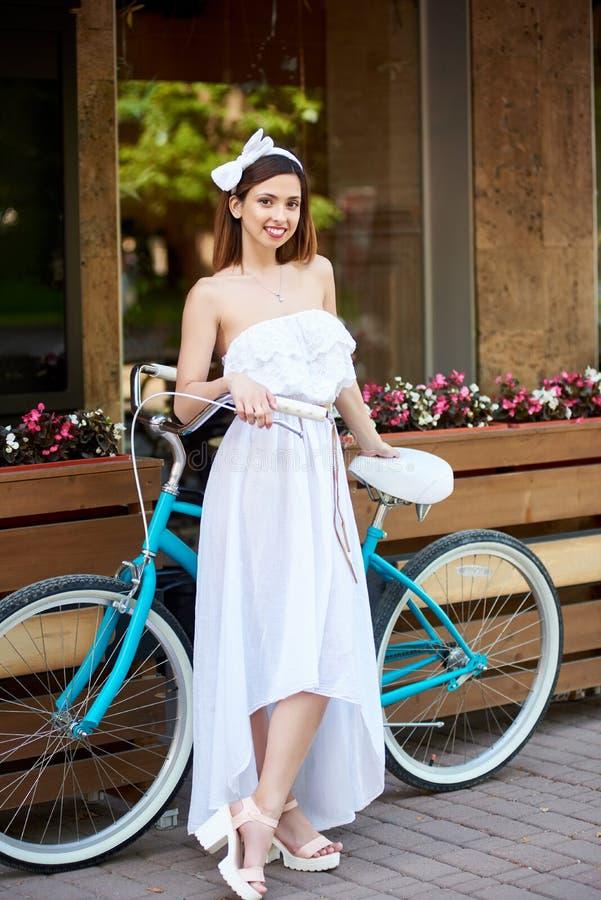 Menina bonita no vestido branco que levanta com bicicleta azul perto de um café imagem de stock