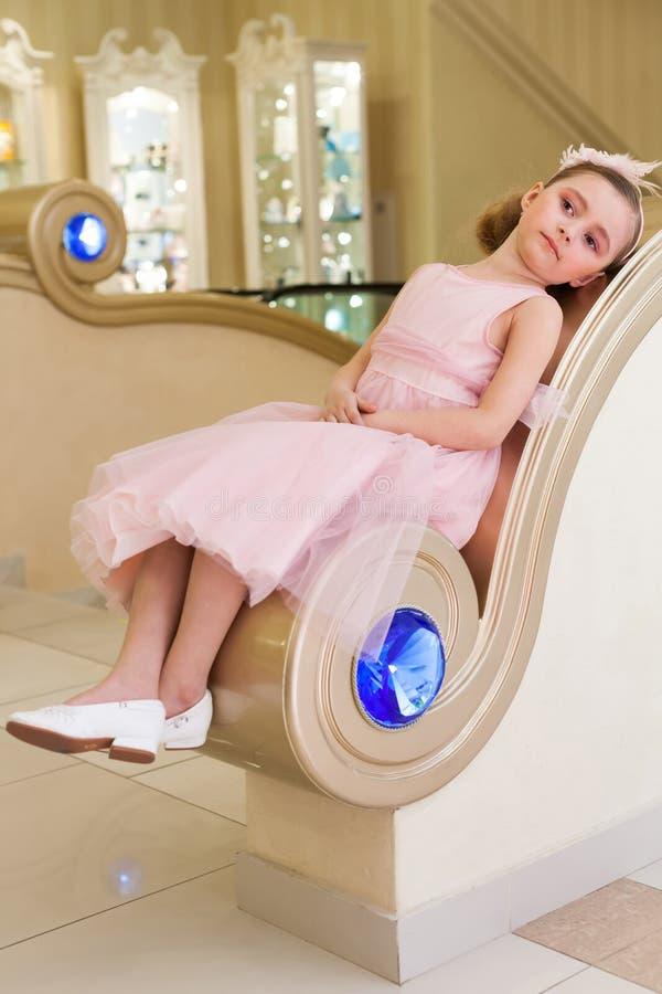 A menina bonita no vestido cor-de-rosa é mentiras nos trilhos fotografia de stock
