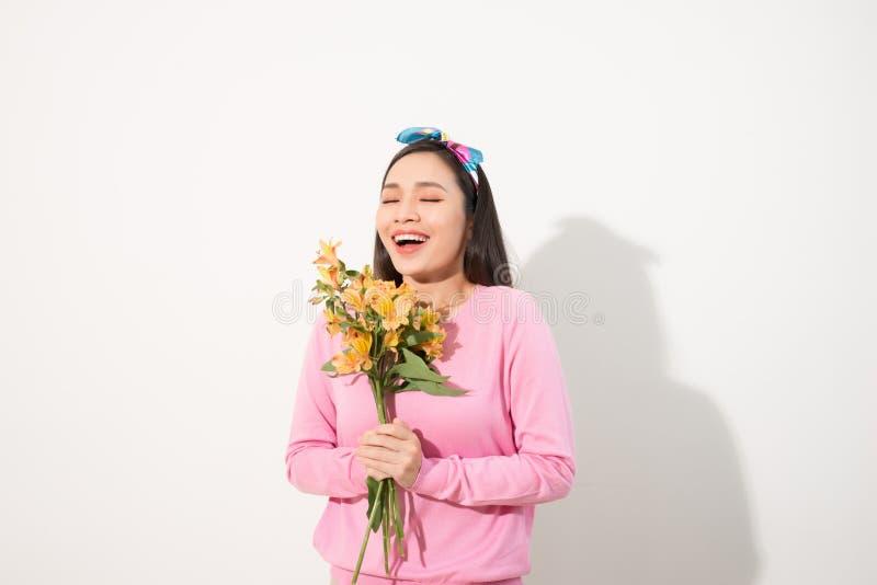 Menina bonita no vestido cor-de-rosa com as flores nas mãos em um whit foto de stock royalty free