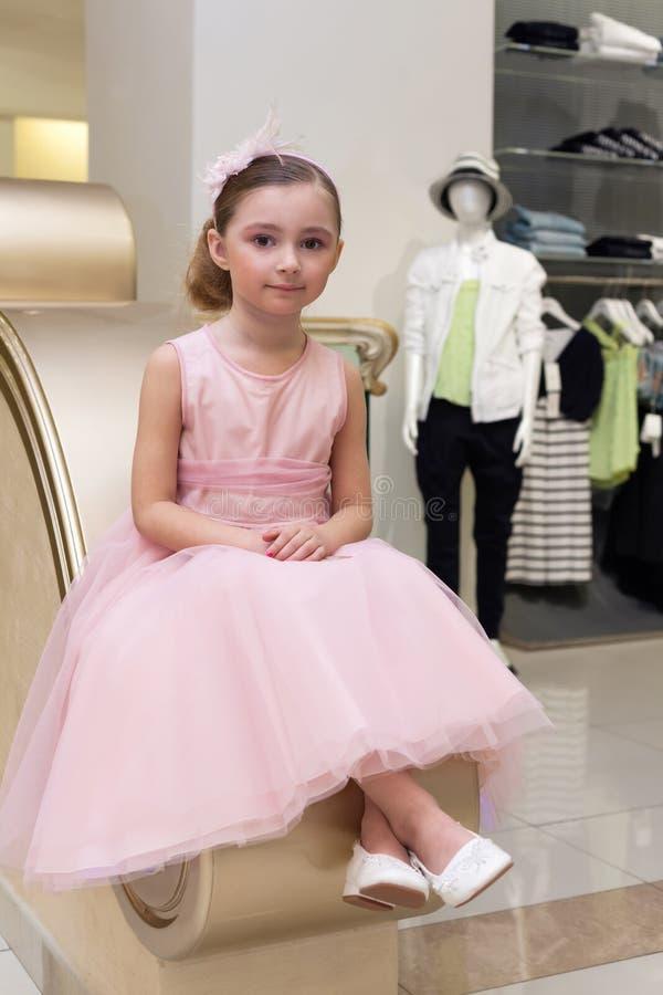 A menina bonita no vestido cor-de-rosa está sentando-se nos trilhos fotos de stock royalty free