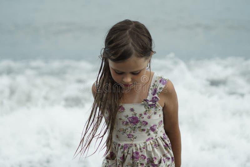 Menina bonita no vestido do ver?o com suportes molhados do cabelo pensativamente pelo mar fotografia de stock
