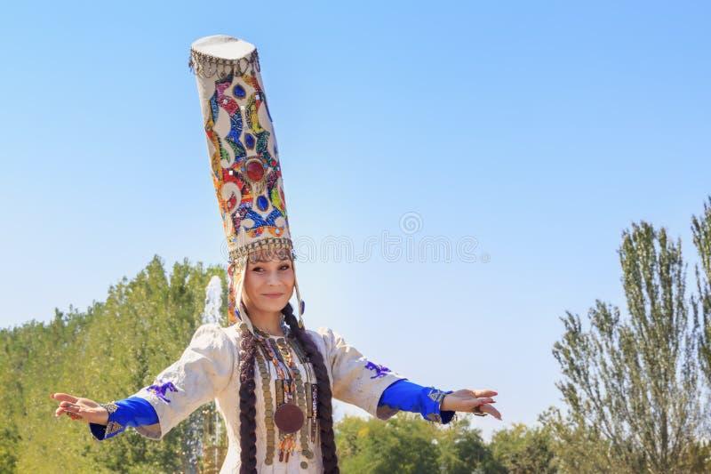 A menina bonita no vestido nacional dança contra o céu azul em um dia ensolarado fotografia de stock royalty free