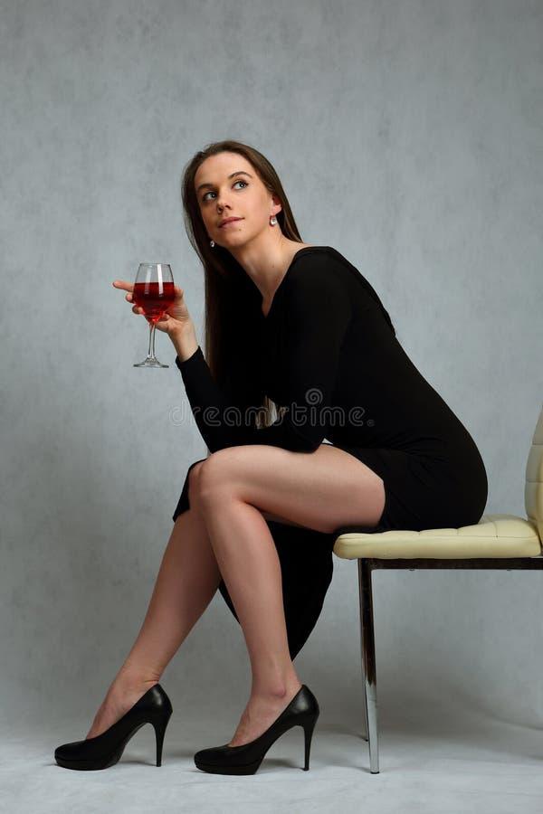 Menina bonita no vestido preto com um vidro do vinho imagem de stock royalty free