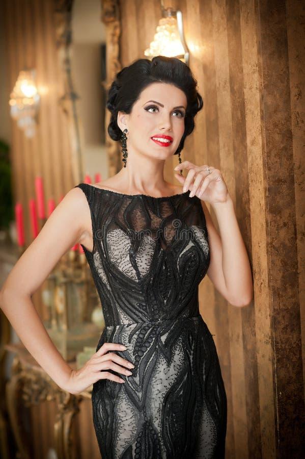 Menina bonita no vestido preto elegante que levanta na cena do vintage Mulher bonita nova que veste o vestido luxuoso Brunette se imagem de stock