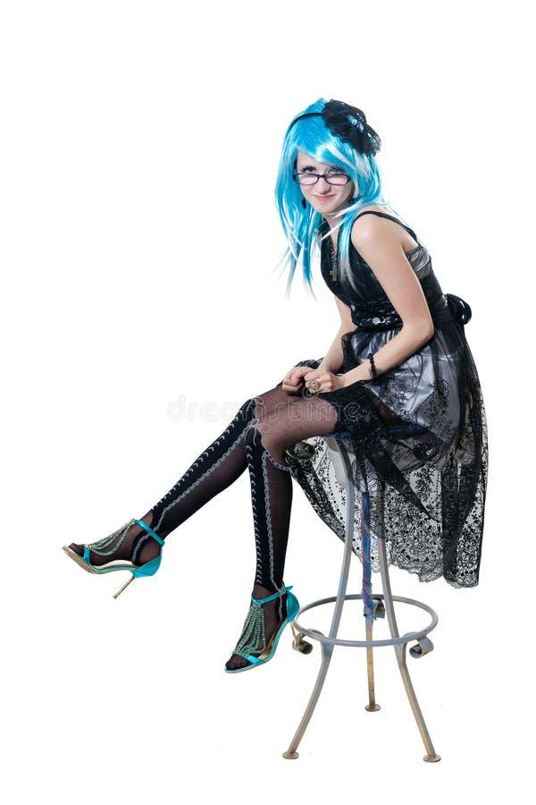 Menina bonita no vestido preto que senta-se na cadeira foto de stock