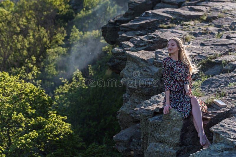 A menina bonita no vestido senta-se na rocha na natureza foto de stock royalty free