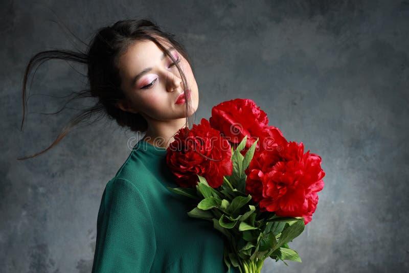 Menina bonita no vestido verde com as peônias das flores nas mãos em um claro - fundo cinzento Modelo fêmea asiático alegre que l fotografia de stock royalty free