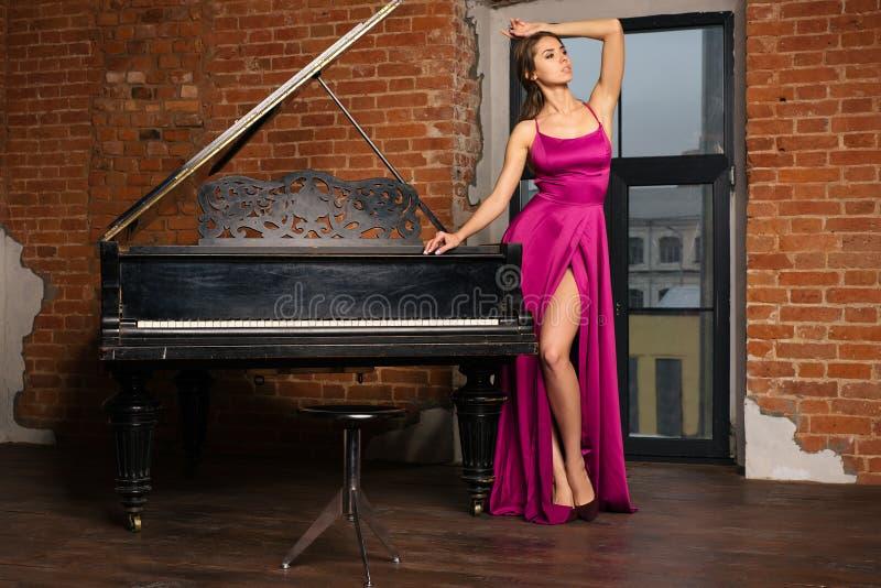 Menina bonita no vestido vermelho clássico longo que levanta com piano velho foto de stock royalty free