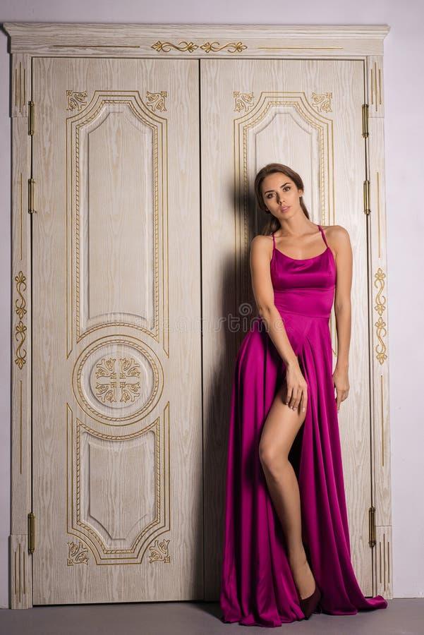 Menina bonita no vestido vermelho clássico longo que levanta perto das portas luxuosas velhas fotos de stock royalty free