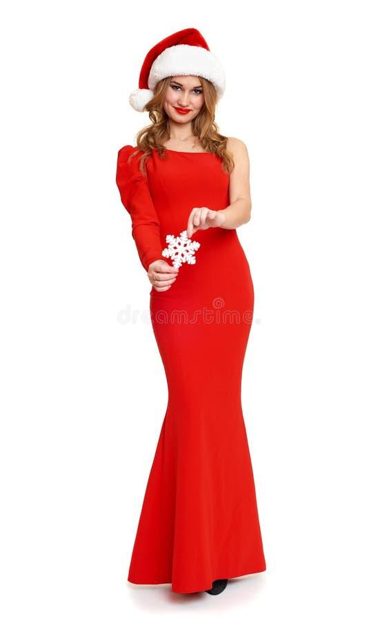 A menina bonita no vestido vermelho e no chapéu de Santa isolados no fundo branco, conceito do feriado do Natal, mostra a decoraç foto de stock