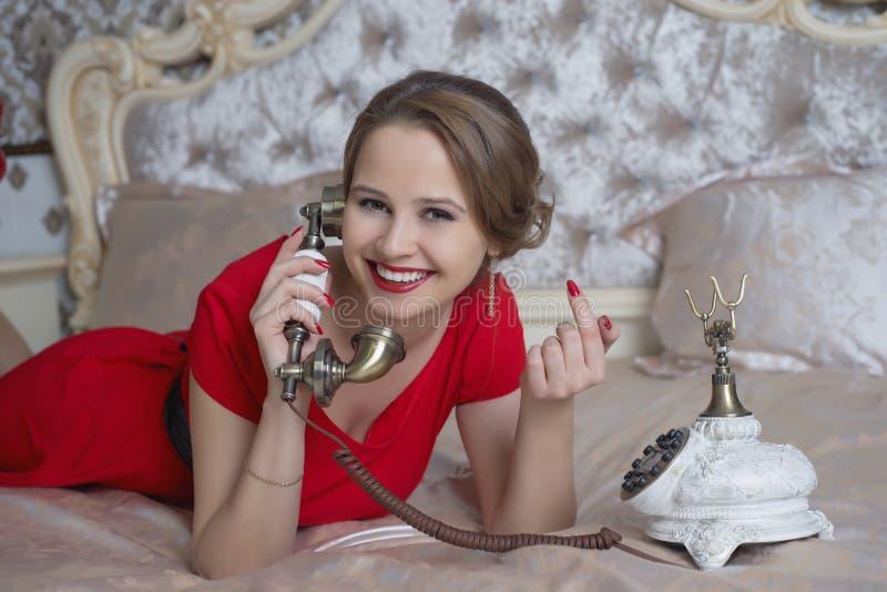 Menina bonita no vestido vermelho que fala no telefone imagens de stock
