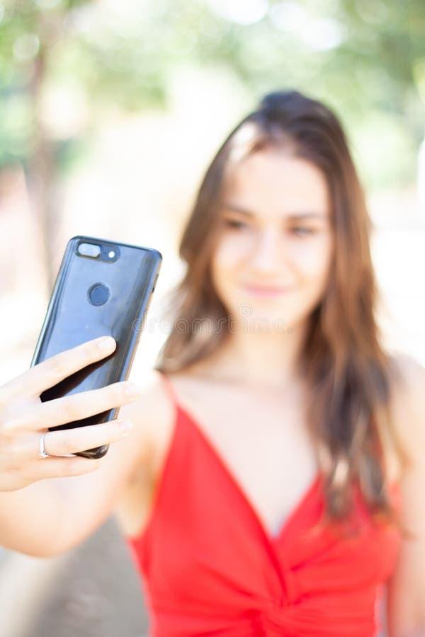 Menina bonita no vestido vermelho que toma o selfie com smartphone fotografia de stock