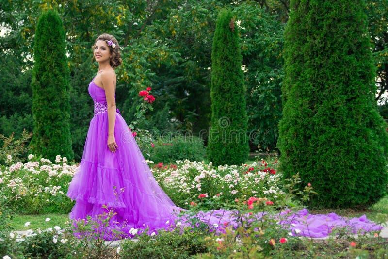Menina bonita no vestido violeta entre no jardim imagem de stock