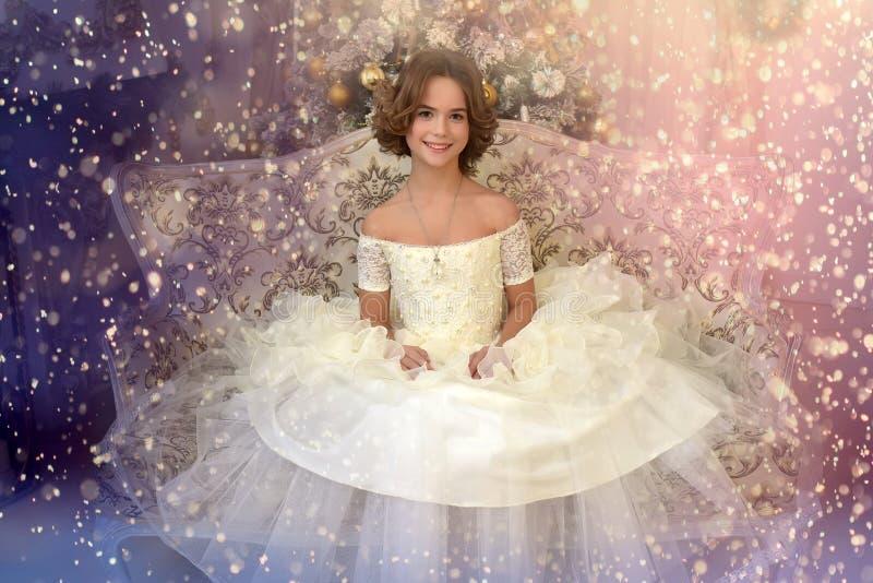 A menina bonita no vestido vitoriano branco na árvore de Natal é imagem de stock