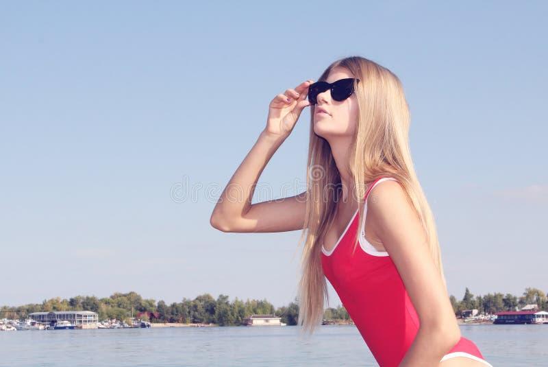 Menina bonita nos óculos de sol e no roupa de banho vermelho imagem de stock