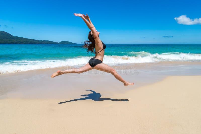 Menina bonita nos biquinis que saltam na praia tropical imagem de stock