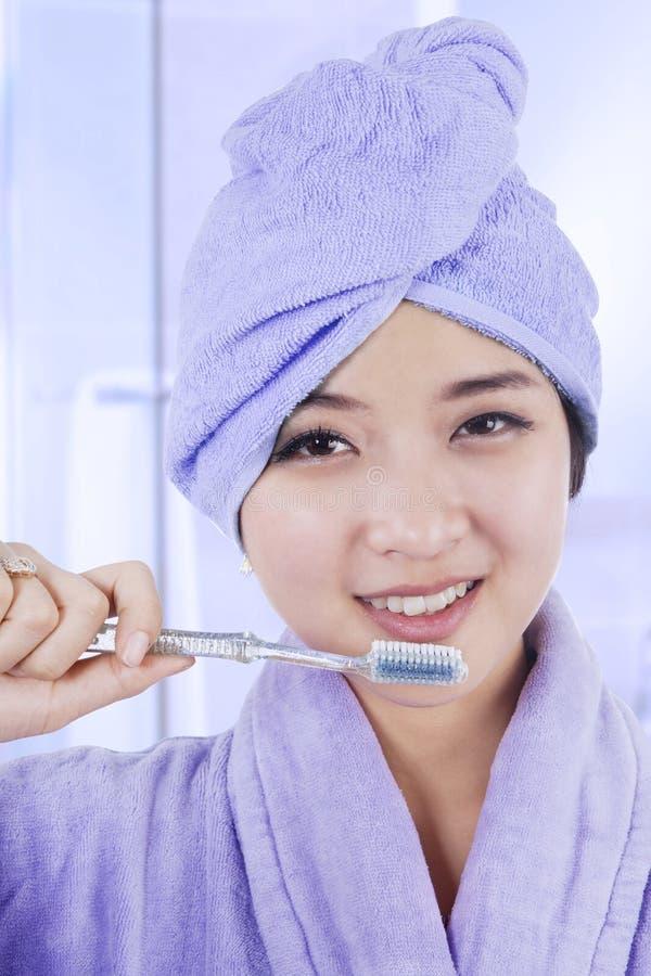 Menina bonita nos dentes de escovadela do roupão foto de stock royalty free