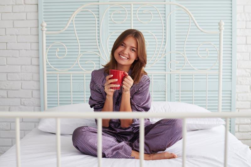 Menina bonita nos pijamas que sentam-se na cama com copo e o smilin vermelhos foto de stock