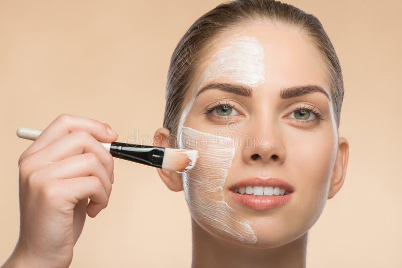 Menina bonita nos termas que aplicam o cosmético facial foto de stock