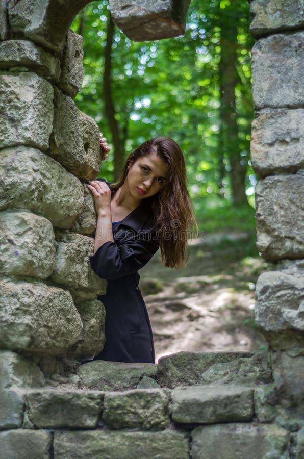 A menina bonita nova com cabelo longo e uma capa de chuva escura olha para fora a janela do castelo velho de que permaneceram som fotografia de stock royalty free