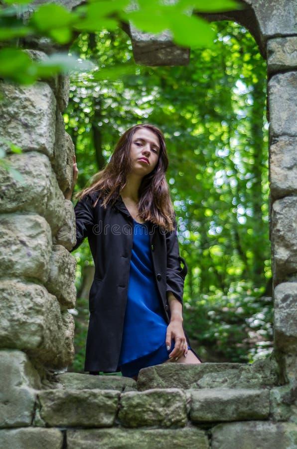 A menina bonita nova com cabelo longo e uma capa de chuva escura olha para fora a janela do castelo velho de que permaneceram som fotografia de stock
