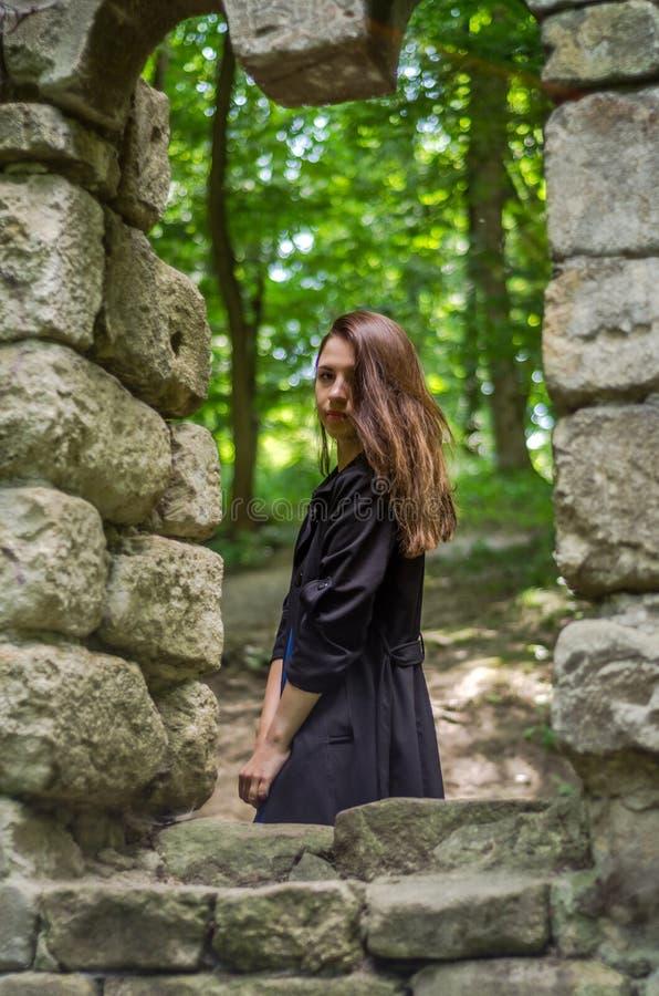 A menina bonita nova com cabelo longo e uma capa de chuva escura olha para fora a janela do castelo velho de que permaneceram som foto de stock royalty free