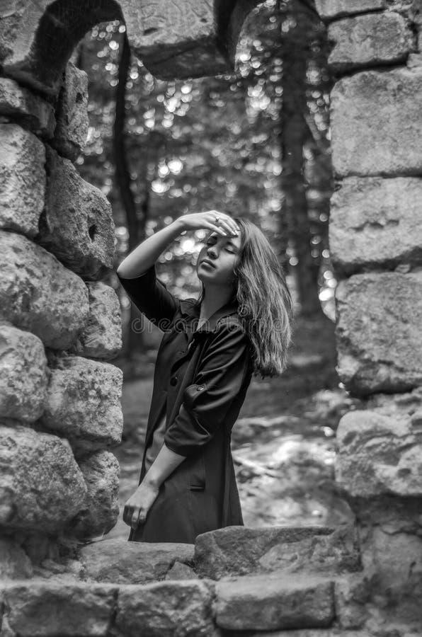 A menina bonita nova com cabelo longo e uma capa de chuva escura olha para fora a janela do castelo velho de que permaneceram som imagens de stock