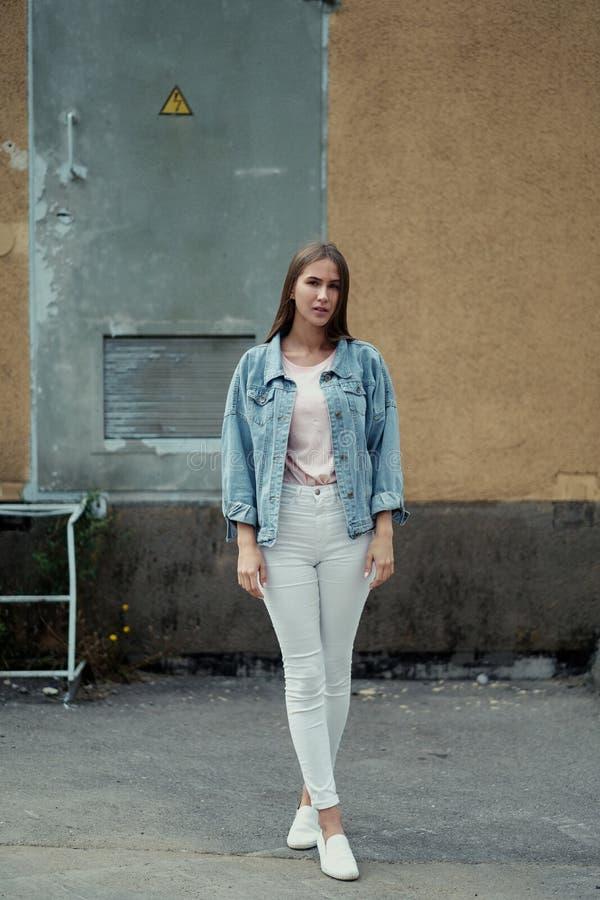 Menina bonita nova com cabelo longo em um revestimento do t-shirt e da sarja de Nimes no fundo do muro de cimento do vintage fotos de stock