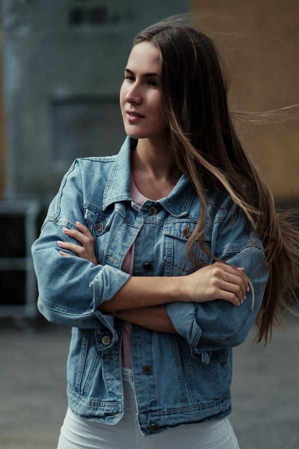 Menina bonita nova com cabelo longo em um revestimento do t-shirt e da sarja de Nimes no fundo do muro de cimento do vintage imagens de stock