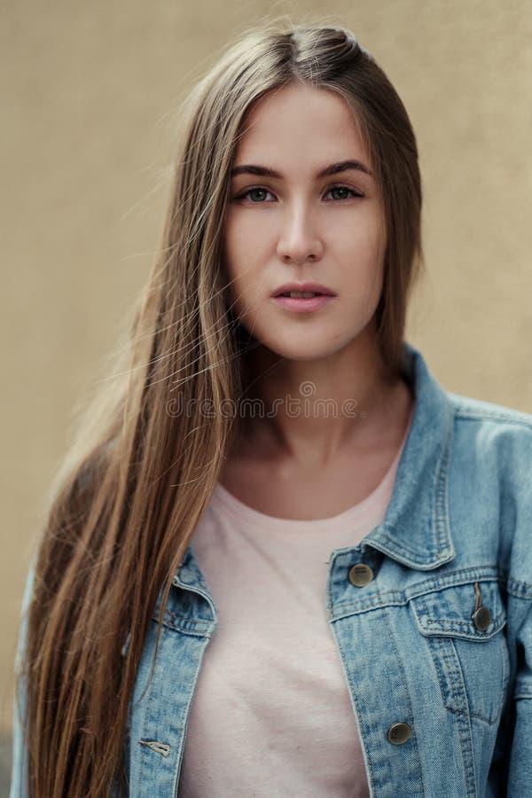 Menina bonita nova com cabelo longo em um revestimento do t-shirt e da sarja de Nimes no fundo do muro de cimento do vintage imagem de stock