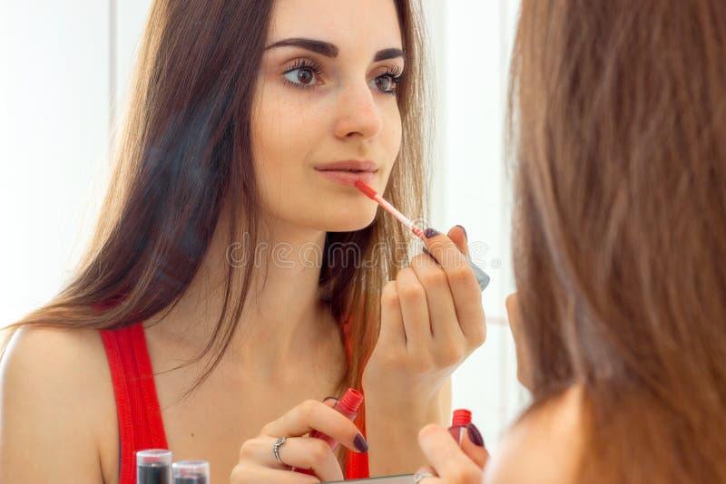 A menina bonita nova com cabelo longo olha nos bordos do espelho e da pintura fotografia de stock