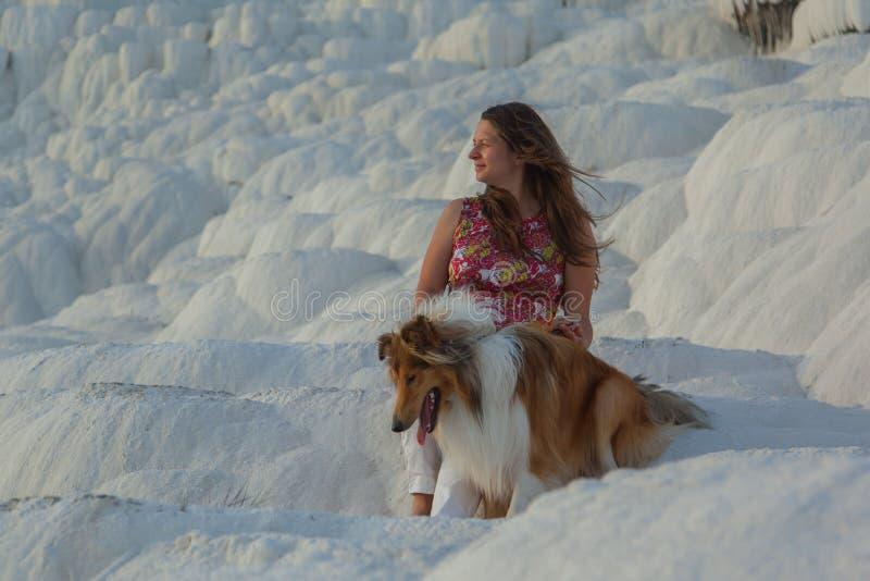 Menina bonita nova com o cão áspero da collie que olha de lado de assento na rocha branca fotografia de stock