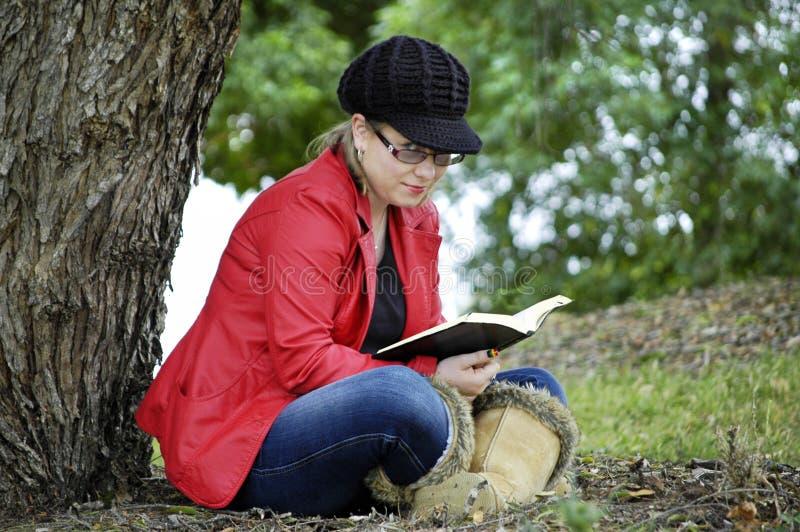 Menina bonita nova com o livro de leitura de relaxamento da expressão insolente no campo fotos de stock royalty free