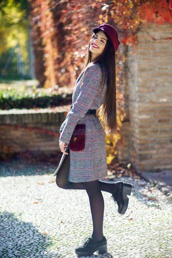 Menina bonita nova com o revestimento e o tampão vestindo do inverno do cabelo muito longo foto de stock