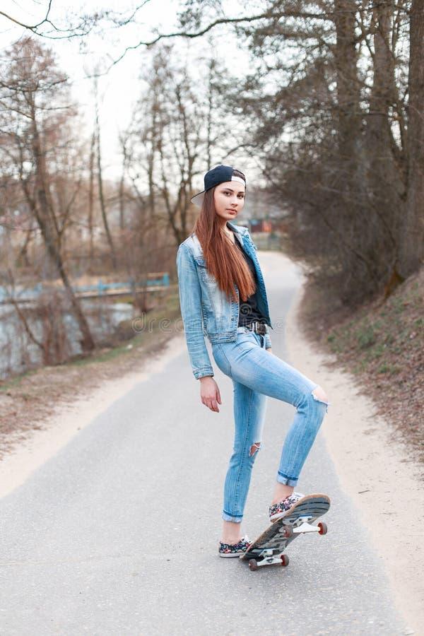 Menina bonita nova com o skate que está na pancadinha do asfalto imagens de stock