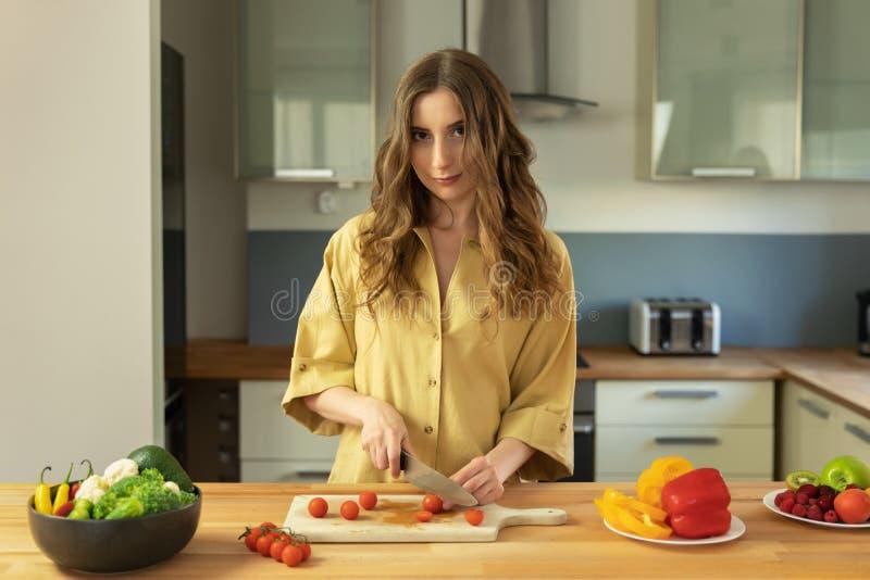 Menina bonita nova com os tomates de cereja longos das fatias do cabelo fotos de stock royalty free