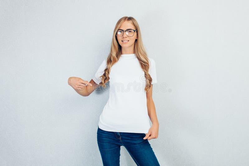 Menina bonita nova com os vidros que vestem o t-shirt branco que aponta o dedo no t-shirt vazio isolado no fundo cinzento imagem de stock royalty free