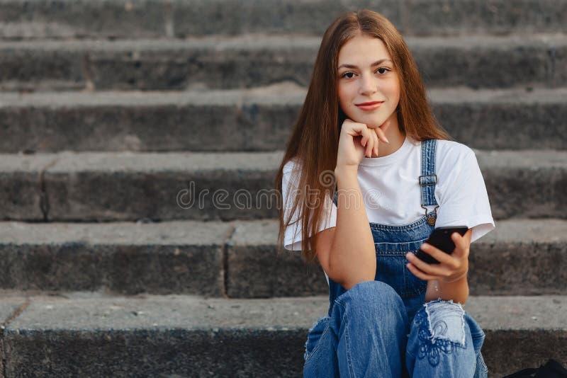 Menina bonita nova com a pasta que senta-se em escadas e que escreve s imagem de stock royalty free