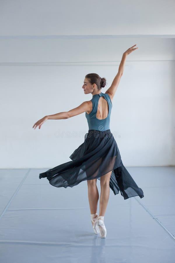 A menina bonita nova com pele bronzeada dança no estúdio Bailarina que gira na dança foto de stock