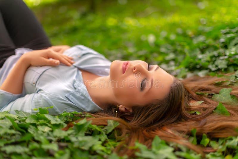 A menina bonita nova com pele perfeita e composição está descansando no parque, no prado da hera da mola Apreciação lindo do ar l fotos de stock