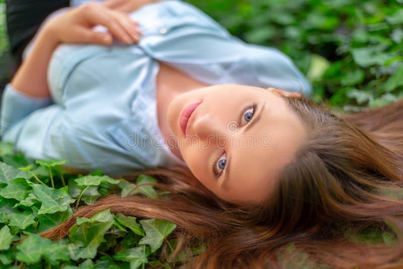 A menina bonita nova com pele perfeita e composição está encontrando-se para baixo no prado da hera, no cenário do parque da mola foto de stock royalty free