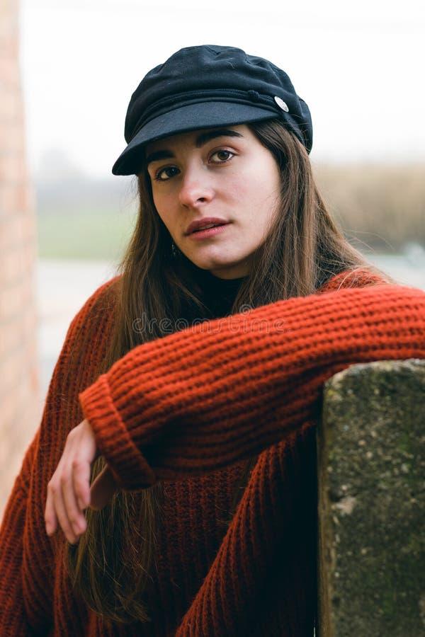 Menina bonita nova com um chapéu e um levantamento alaranjado da camiseta sérios na câmera Ao ar livre retrato da forma foto de stock