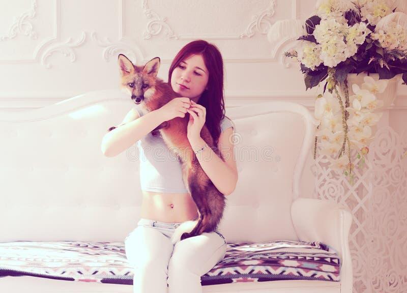 Menina bonita nova com uma raposa imagem de stock royalty free